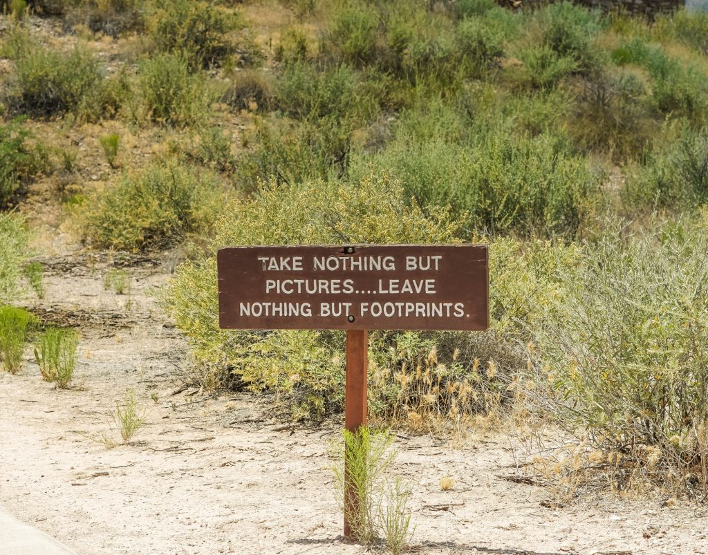 "Sign on trail to ancient ruins that says ""Take nothing but pictures..leave nothing but footprints ""-"